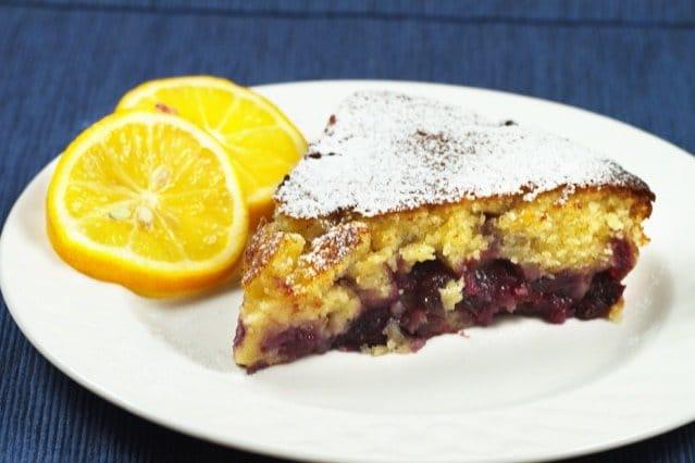 slice of Meyer lemon, blueberry butter cake on a white plate with slices of Meyer lemons