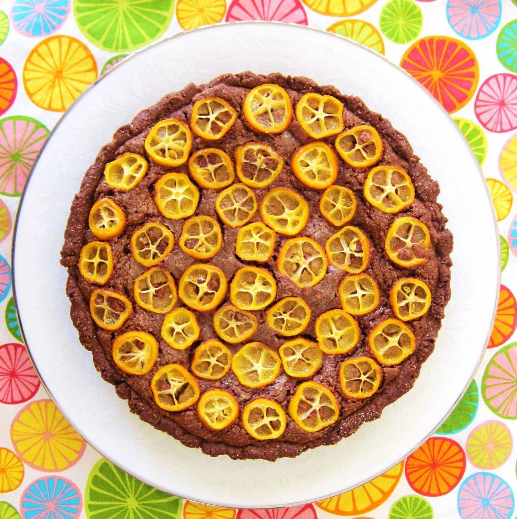 overhead shot of chocolate citrus frangipane tart with sliced kumquats on top