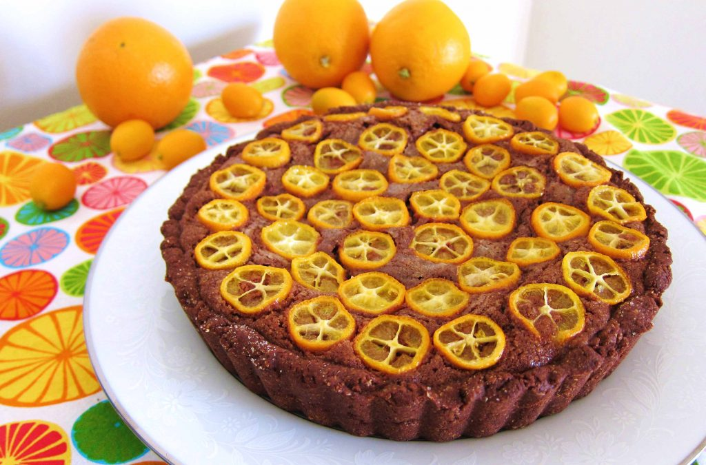 angled shot of chocolate citrus frangipane tart with sliced kumquats on top