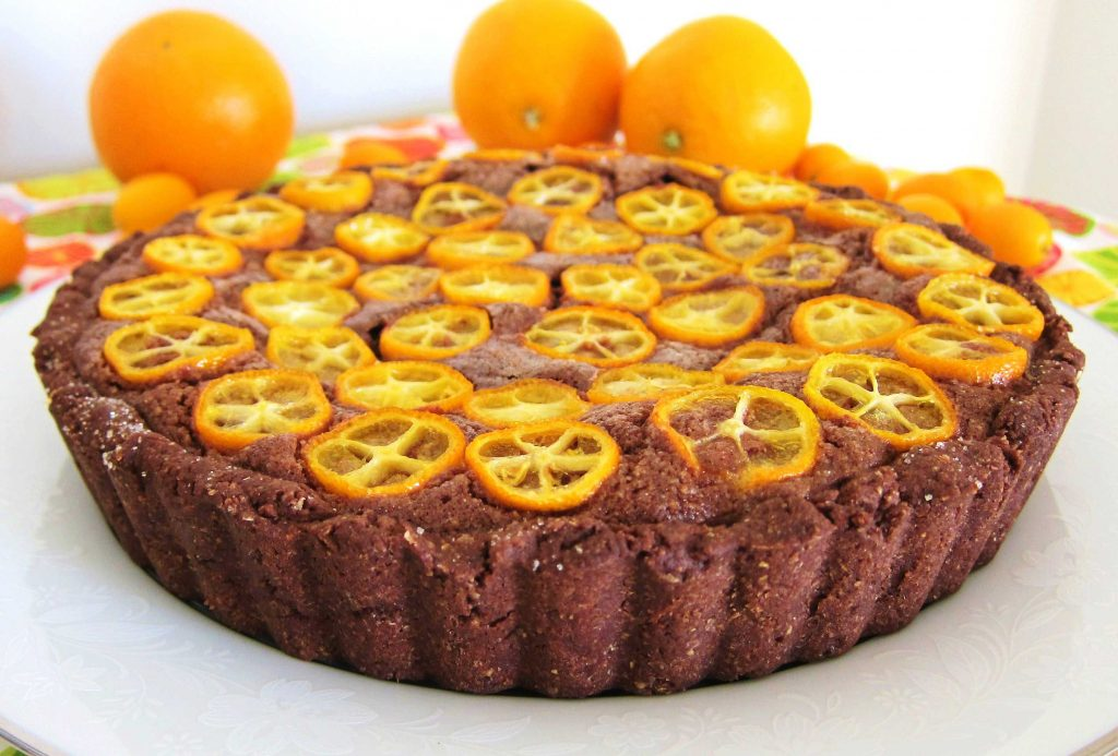side view of chocolate citrus frangipane tart with sliced kumquats on top