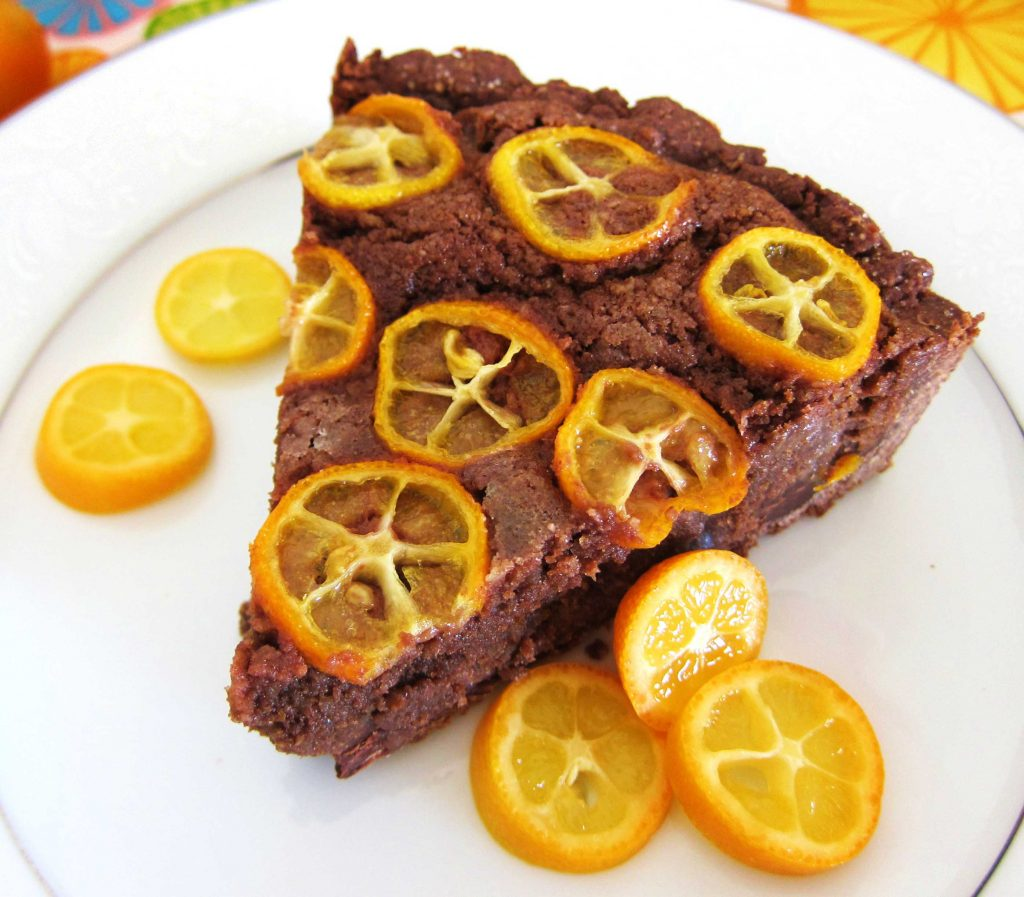 slice of chocolate citrus frangipane tart with sliced kumquats on top on a white plate