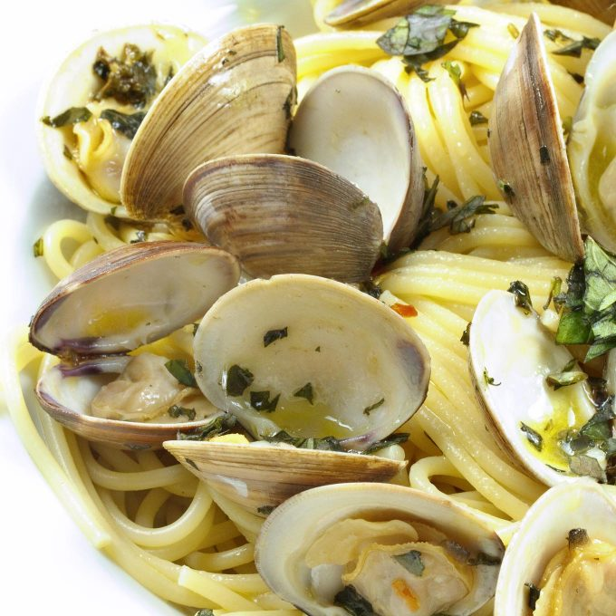 close up of Linguine with clams in a white bowl with a chopped basil garnish