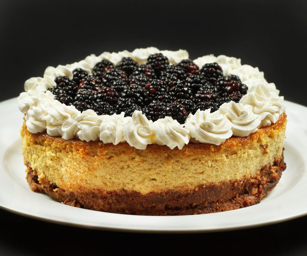 whole ricotta cheesecake with blackberries and whipped cream on a white platter