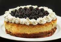 ricotta cheesecake topped with whipped cream and blackberries on a white platter