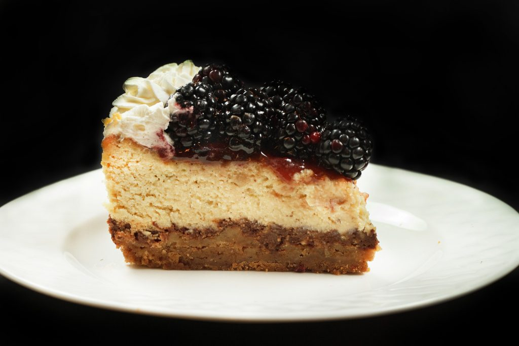 slice of ricotta cheesecake topped with blackberries on a white plate on a black background