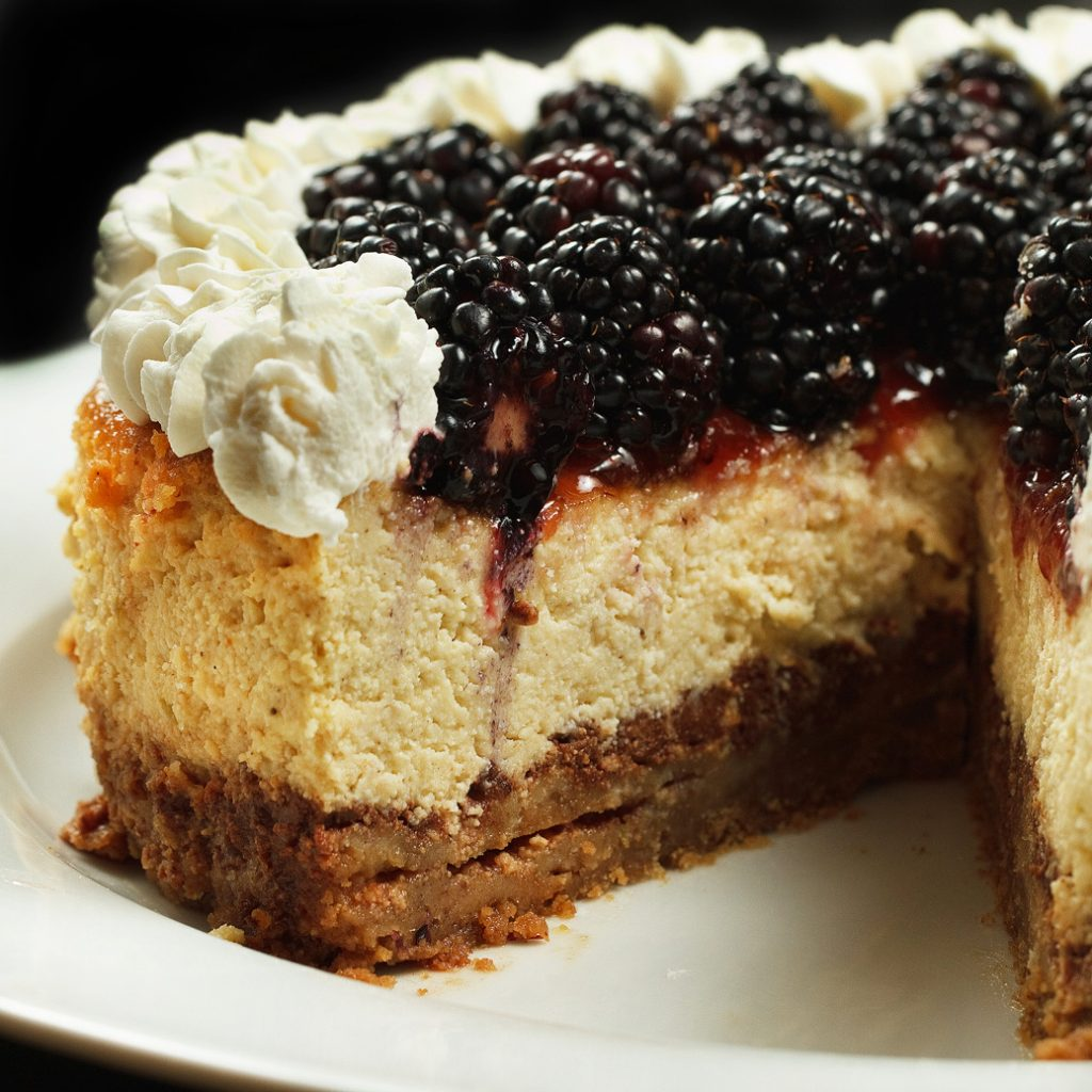 whole ricotta cheesecake with a slice missing topped with blackberries and whipped cream