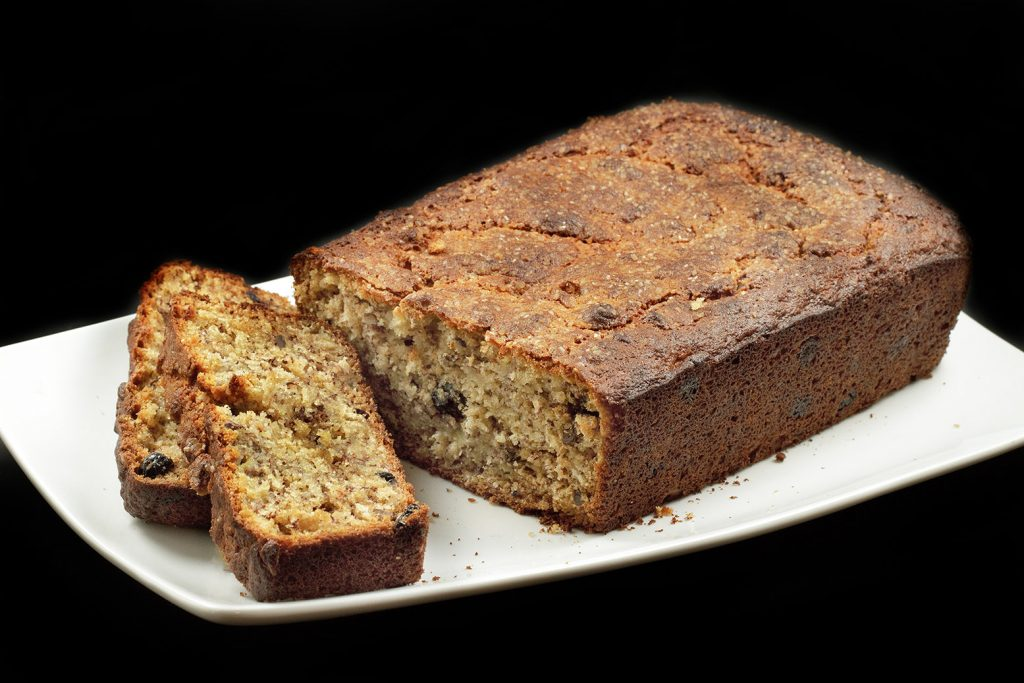 Blueberry oat Banana bread with Pecans with two slices sitting in front of the whole cake on a white plate on a black background