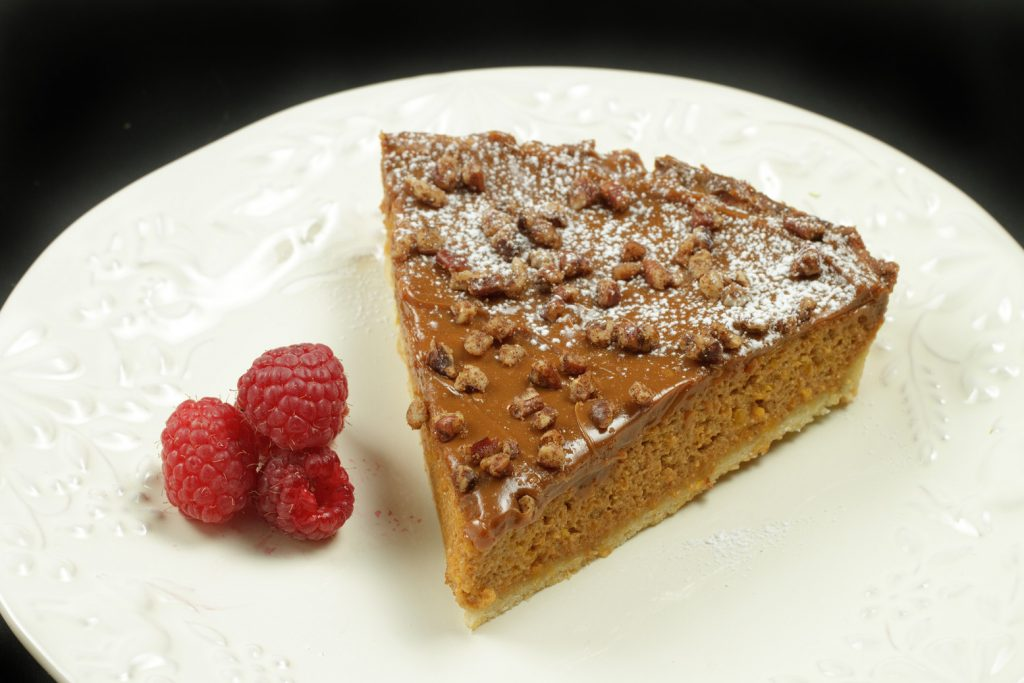 slice of caramel butternut squash torte with cinnamon pecans on a white plate with 3 raspberries