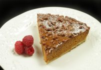 slice of butternut squash caramel torte on a white plate with raspberries
