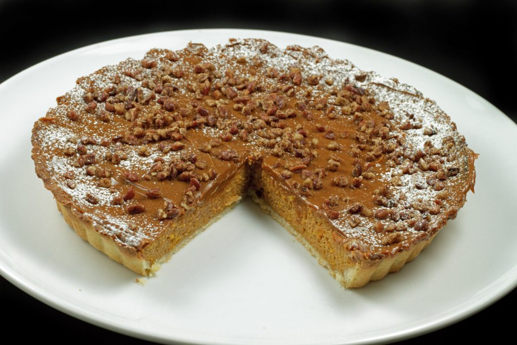 overhead picture of caramel butternut squash torte with cinnamon pecans on a white plate with a slice missing