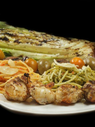 grilled romaine, pasta and grilled lobster on a white platter