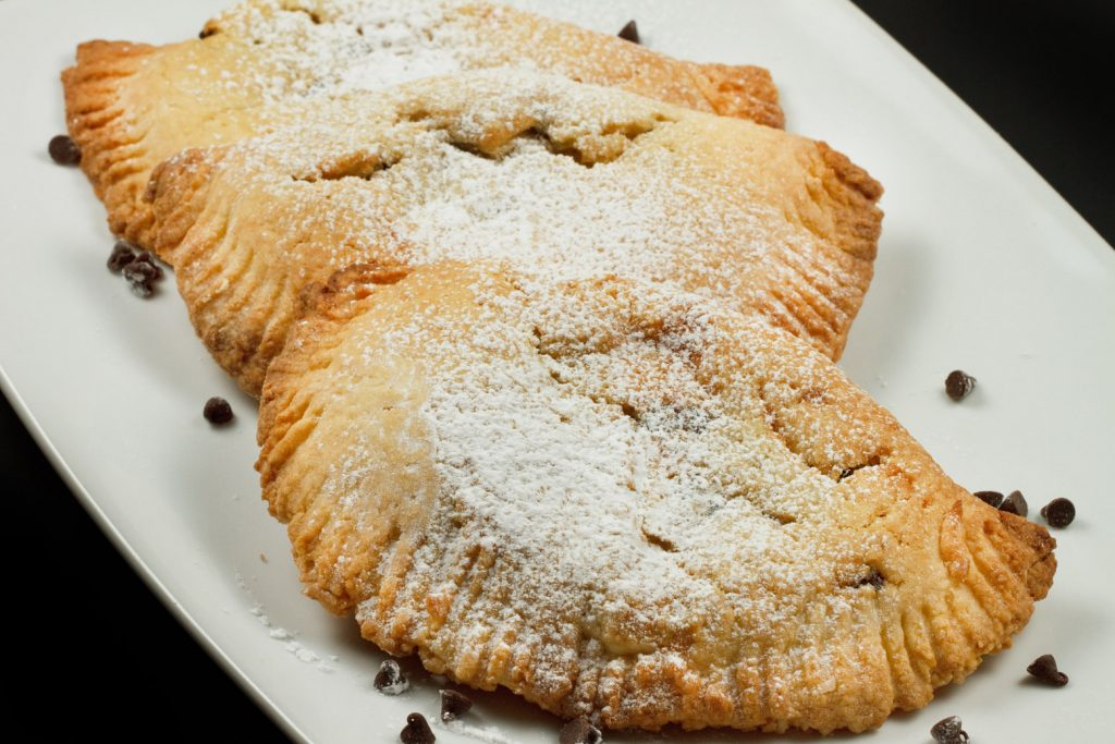 3 sweet ricotta hand pies dusted with confectioners sugar on a white plate