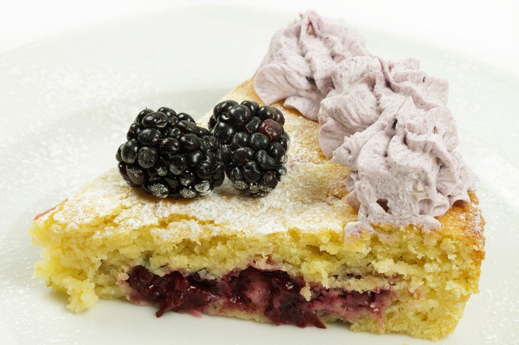 slice of blackberry lime butter cake with blackberry whipped cream and blackberries