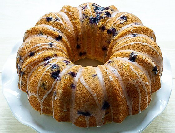 gluten free lemon pound bundt cake with blueberries on a white plate