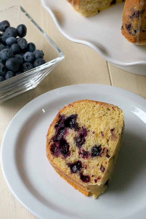 slice of gluten free lemon pound cake with blueberries on a white plate with a bowl of blueberries and the rest of the cake sitting on a table