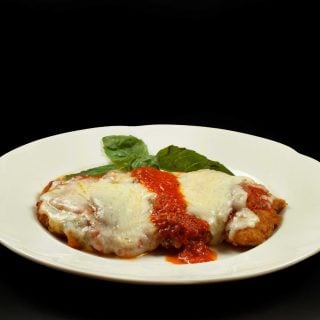 chicken parmesan on a white plage with a sprig of basil