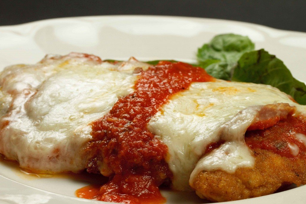 A close up of chicken parm on a white plate