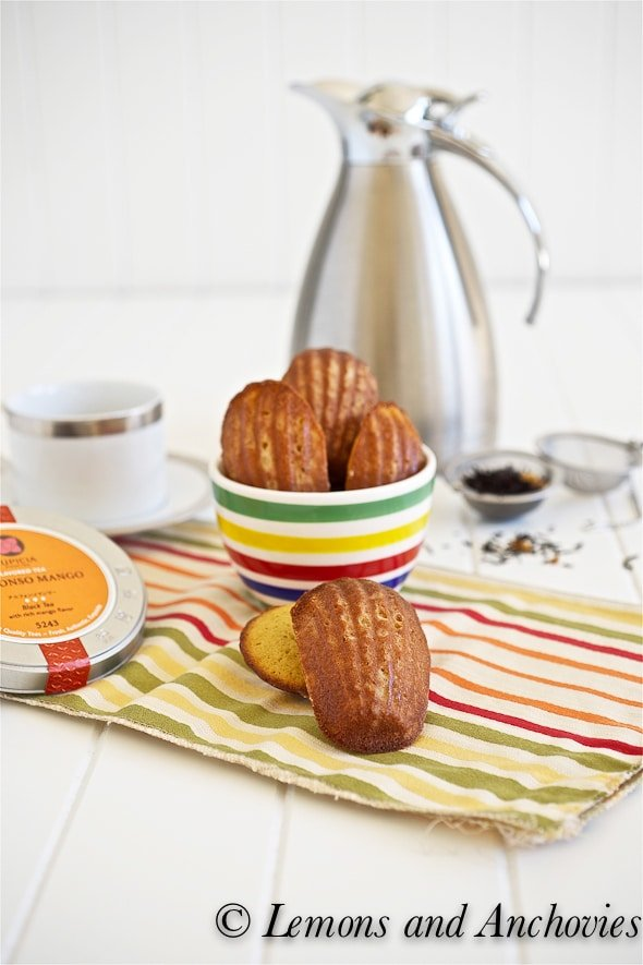 honey mango Madeleines on a striped dish cloth on a white table with a tea pot and tea cup