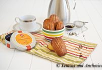 bowl of madeleines on a striped tablecloth with more madeleines and tea service