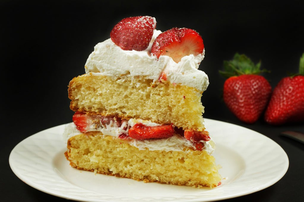 slice of strawberry cream cake on a white plate with strawberries in the background