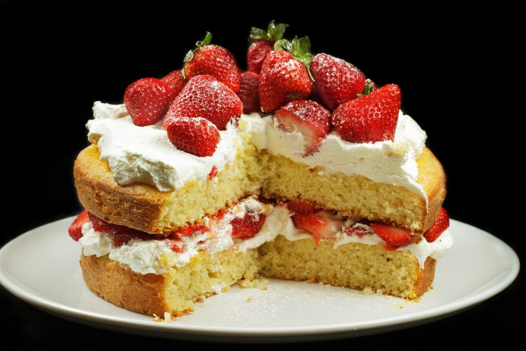 Strawberry Cake with Cream on a white platter with 1/4 of the cake cut out