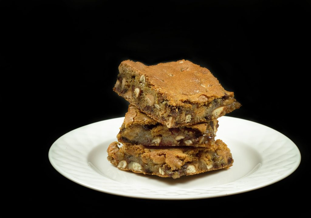 3 Peanut Butter Pretzel Blondies stacked on a white plate
