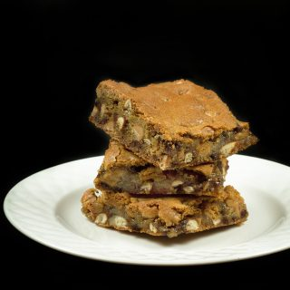 stack of 3 peanut butter pretzel blondies on a white plate