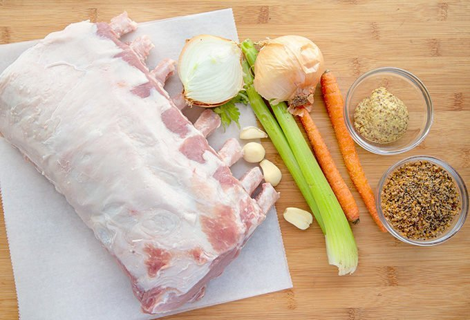 raw bone in rack of pork with seasonings  and vegetables on a wooden cutting board