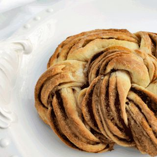 braided orange cinnamon vanilla pastry on a white plate