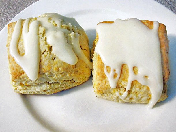 close up of 2 orange cardamom scones on a white plate