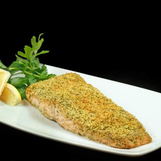 Matcha Green Tea Salmon on a white plate with a sprig of parsley and lemon slices