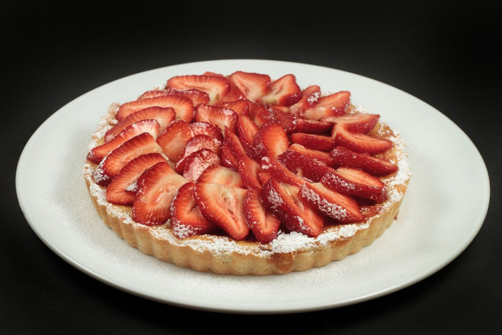strawberry ricotta crostata on a white plate on a black background