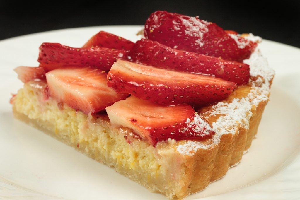 slice of a strawberry ricotta crostata on a white plate