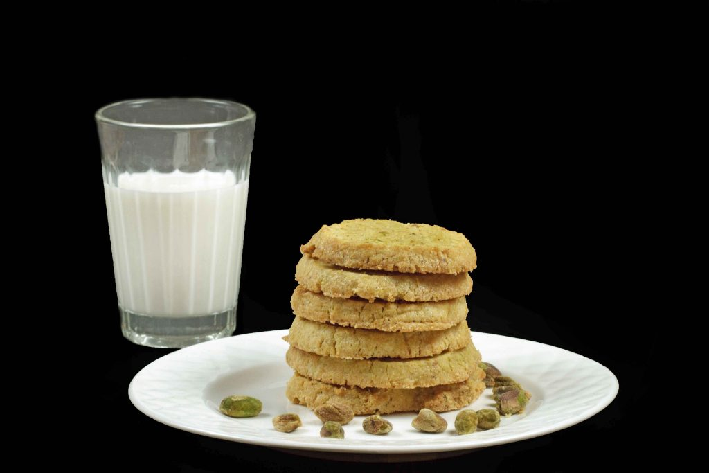 stack of pistachio cornmeal cookies sitting on a white plate on a black background with a glass of milk