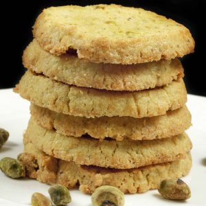 stack of pistachio cornmeal butter cookies on a white plate with pistachios
