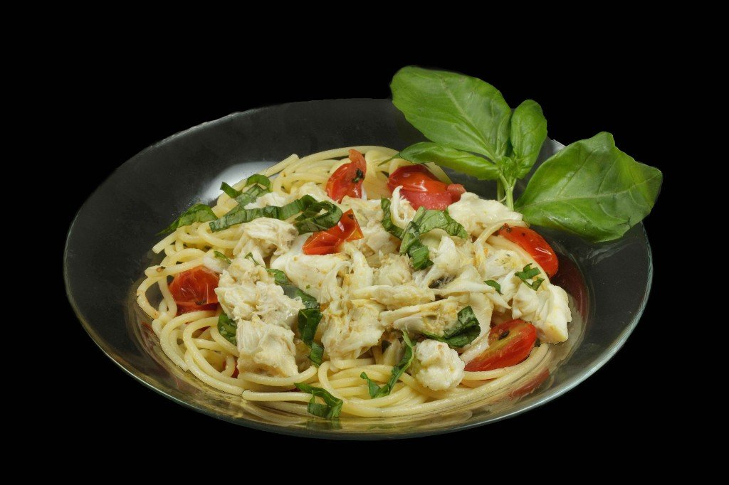 A black bowl of pasta topped with jumbo lump crabmeat, basil and tomatoes