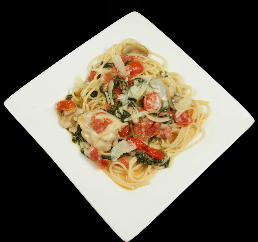 chicken marsalena with pepperoni over linguine on a white plate on a black background