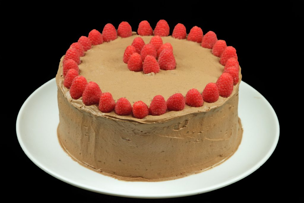 Whole chocolate mousse cake decorated with raspberries on a white serving plate on a black background