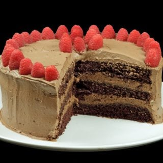 three-layer chocolate cake with raspberries with section cut out on a white platter