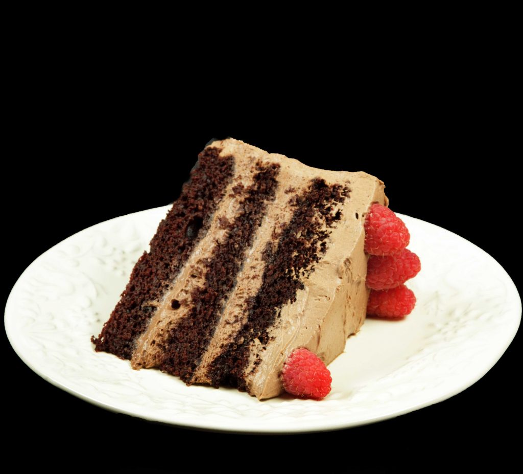 slice of chocolate mousse cake on a white plate on a black background