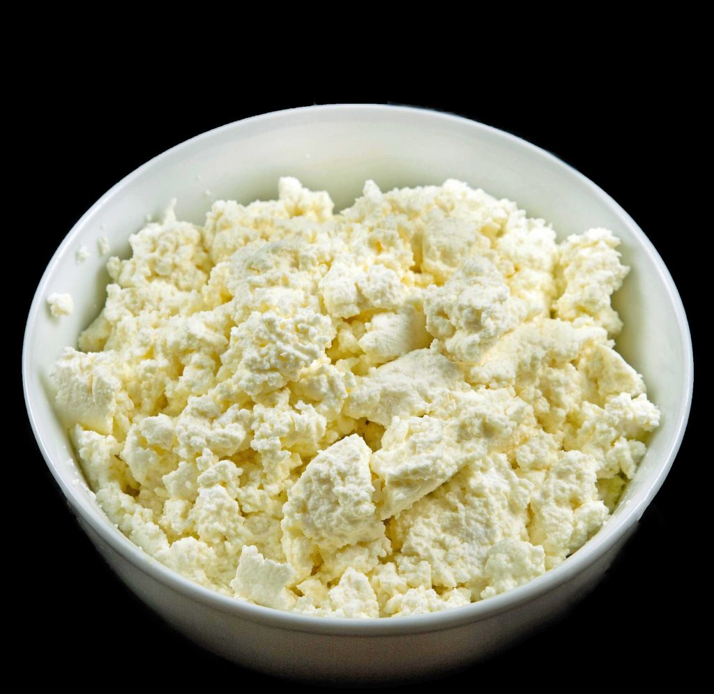 homemade ricotta cheese curds in a white bowl on a black background