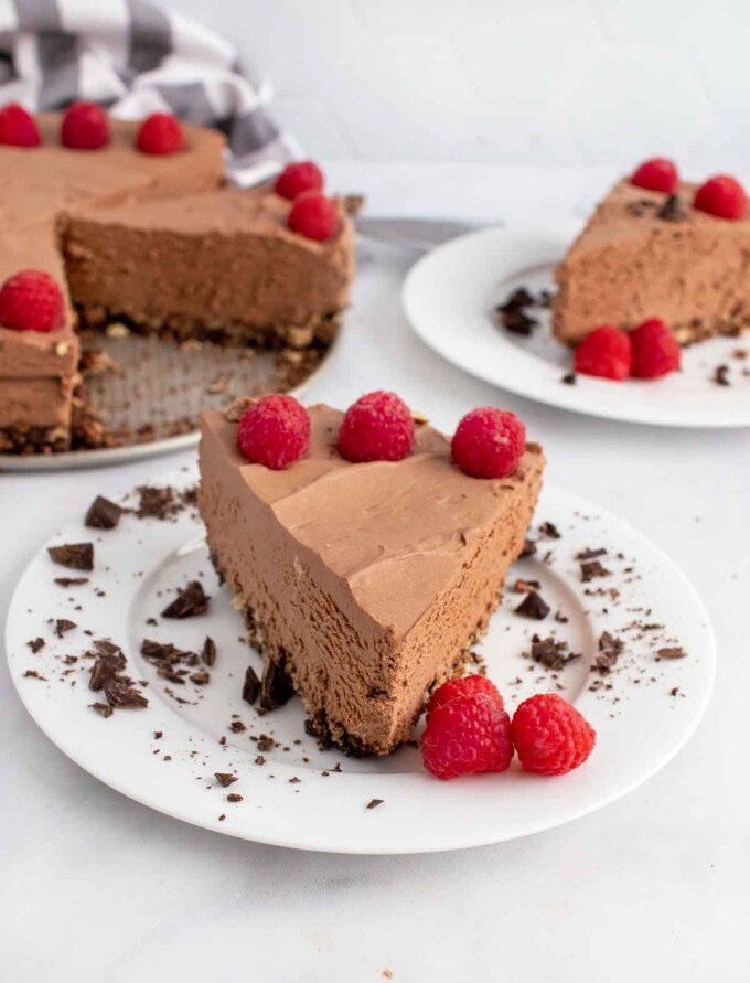slice of no bake chocolate cheesecake on a white plate with another slice and the whole cheesecake behind it