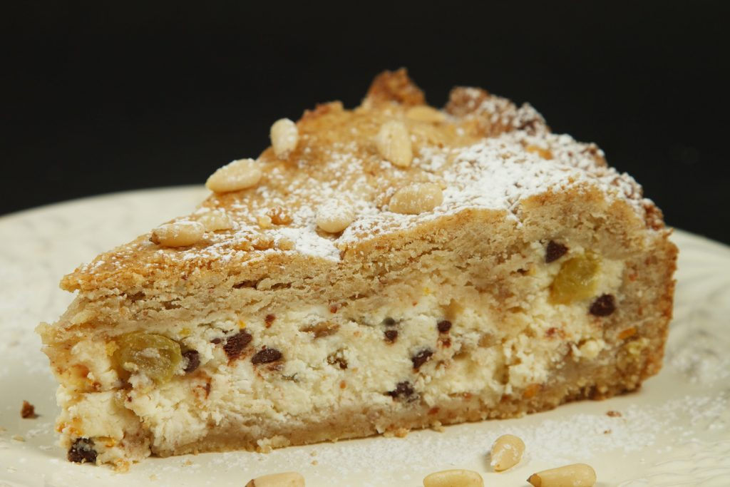slice of Torta di Ricotta on a white plate with a sprinkling of confectioners sugar and pine nuts