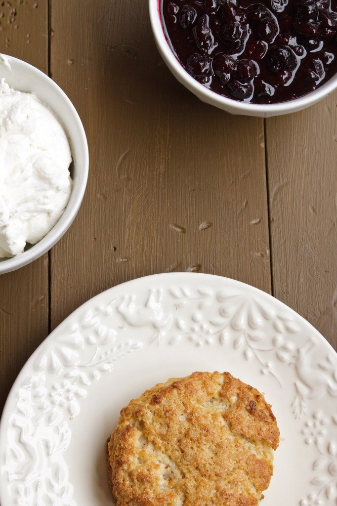 overhead view of scone on a white plate with bowls of blueberry sauce and whipped cream