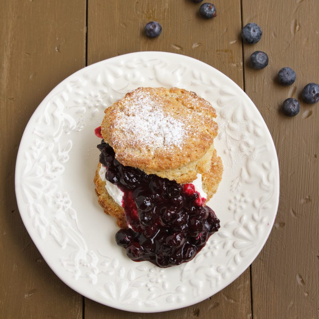 overhead view of spit scone with blueberry sauce on a white plate