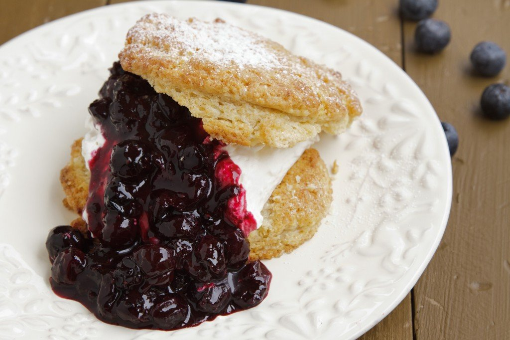 spit scone with blueberry sauce on a white plate