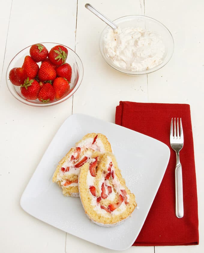 slices of a strawberry shortcake roll on a white plate with a red napkin and a fork, with a bowl of whole strawberries and a bowl of whipped cream