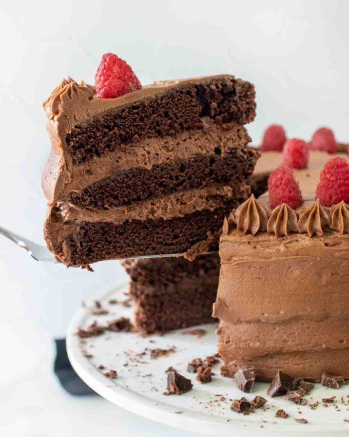 slice of chocolate mousse cake being taken out of whole cake