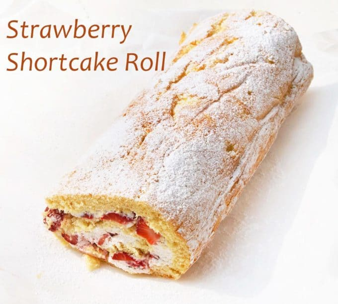 yellow cake made into a roll stuffed with whipped cream and fresh strawberries dusted with powdered sugar