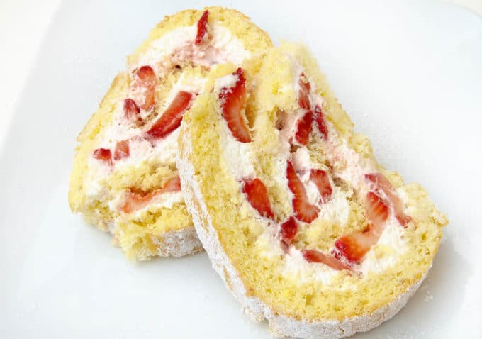 slices of a strawberry shortcake roll on a white plate
